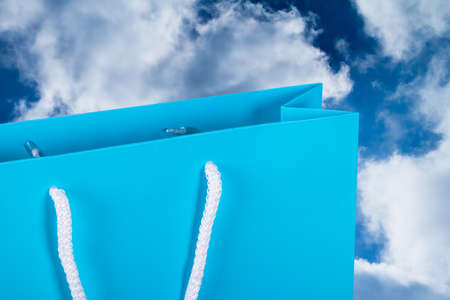 Close up view of blue carton shopping bag with sky background. photo