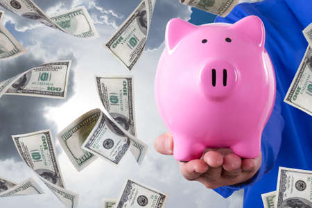 Businessman hand holding pink piggy bank and one hundred dollar banknotes flying around on cloudy sky background. photo