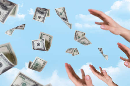 One hundred dollar money banknotes flying and falling on young male hands, cloudy background. Stock Photo