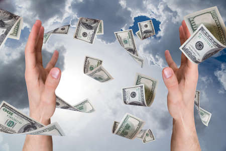 One hundred dollar money banknotes flying and falling on young male hands, cloudy background. photo