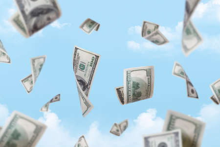 Dollar banknotes falling down with depth of field on cloudy sky background. photo