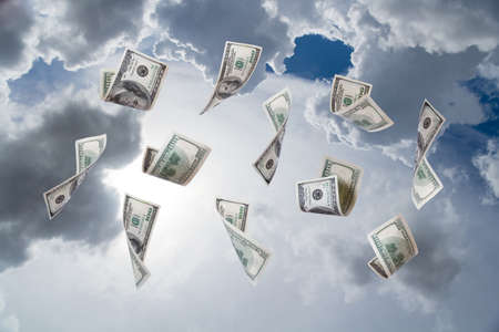 Dollar banknotes falling down on cloudy sky background. photo