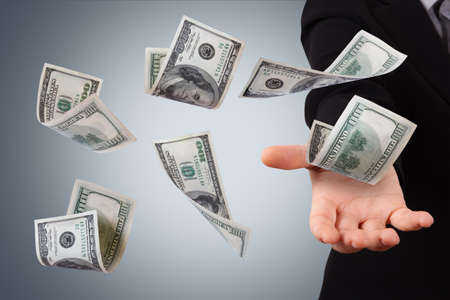 One hundred dollar money banknotes flying and falling on young business woman hand.