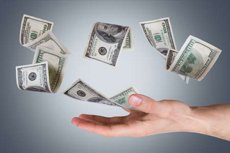 One hundred dollar money banknotes flying and falling on young male hand, side view, dark background. Stock Photo