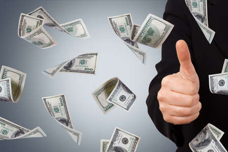 One hundred dollar money banknotes flying and falling down with confirmation sign of young business woman. Stock Photo