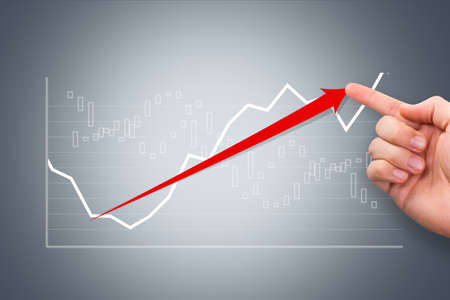 Business and finance concept, young male hand showing graph chart with red arrow on digital screen. photo
