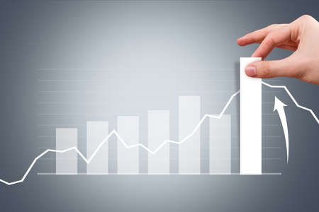 Business and finance concept, young male hand pulling bar of graph chart on digital screen. photo