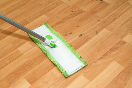 Mop cleaning and washing the wooden parquet floor in room. Stock Photo