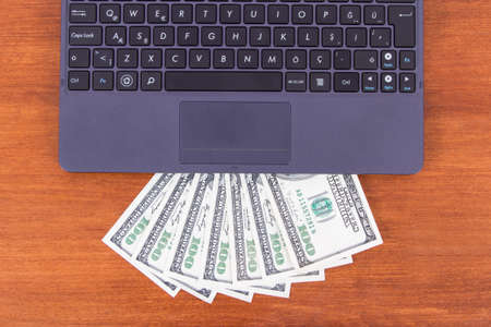 Detail view of laptop and one hundred dollar banknotes on wooden table. photo