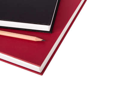 Stack of black and red books with pencil, isolated on white background. photo