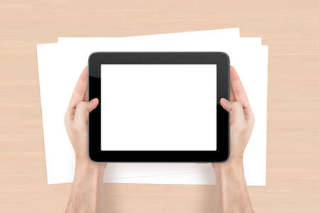 Hand holding tablet with blank, white screen and empty sheet on wooden office table. photo