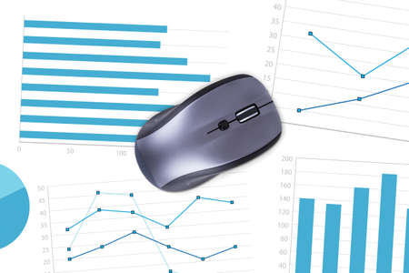 Top view of wireless computer mouse on paper sheet with financial statistic charts. photo