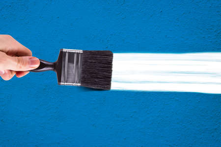 Male hand painting blue wall with white color  using paint brush. photo