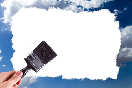 Male hand holding paint brush and painting blue and cloudy sky with copy space for your design, isolated on white background. photo