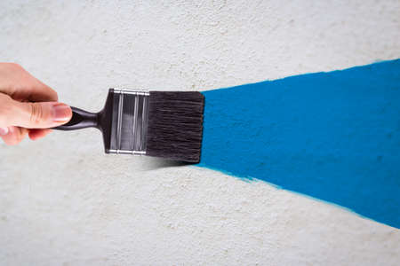 Male hand holding paint brush and painting white wall with blue color.
