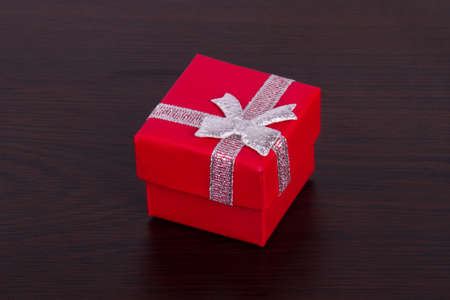 closed ribbon: Red little closed gift box with ribbon ornament on wooden background. Stock Photo