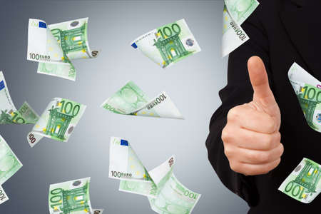 One hundred euro money banknotes flying and falling down with confirmation sign of young business woman. Stock Photo