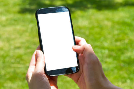multi touch: Young female hand finger touching and using smart phone with blank white screen on green background filled grass.
