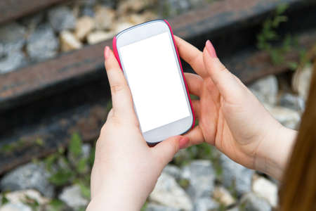 multi touch: Young woman holding and showing smart phone with blank white empty screen on blurry stones and railway background.