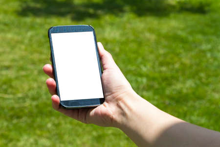 multi touch: Young woman hand holding and showing smart phone with blank white empty in summer on natural green background.