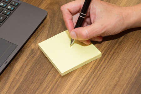 Hand writing on blank, yellow sticky post