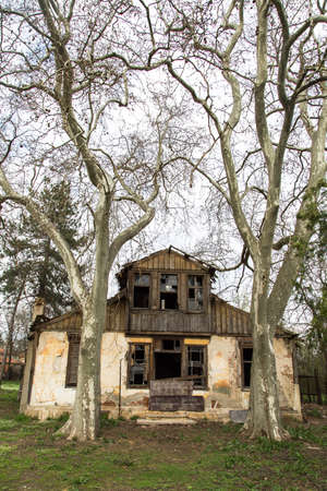 Front view of abandoned old building with dead trees. photo