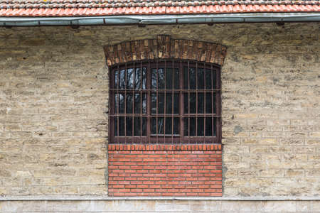 gratings: Front view of old window of stone building with gratings.