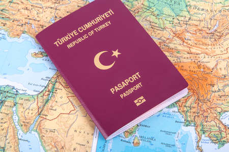 passport: Close up detailed view of a Turkish passport lying on a world map. Stock Photo