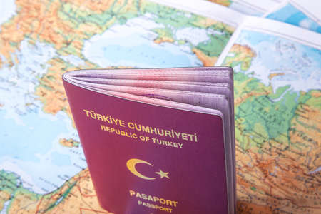 foreign national: Close up detailed view of a Turkish passport standing on a world map.