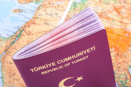 pasaporte: Cerrar la vista detallada de un pasaporte turco de pie sobre un mapa del mundo.