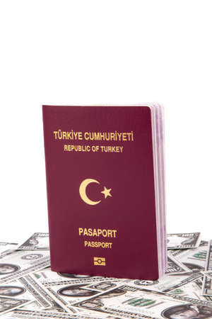 one hundred euro banknote: Close up front view of a Turkish passport on one hundred dollar banknotes, isolated on white background. Stock Photo