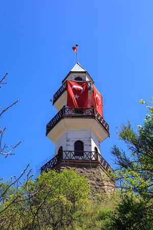 buttom: Buttom view of wooden tower building with Turkish flag waving, under blue sky. Stock Photo