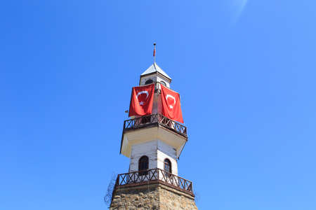 buttom: Detailed buttom view of wooden tower building with Turkish flag waving, under blue sky. Stock Photo