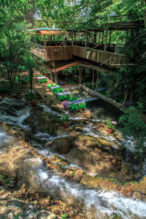 settled: HATAY, TURKEY - JUNE 7, 2015 : Top view of restaurant with colourful table and chairs, settled in Harbiye Waterfall in Antakya.
