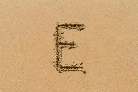 upper case: Letter E of the alphabet written on sand with upper case.