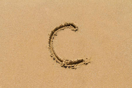 upper case: Letter C of the alphabet written on sand with upper case.