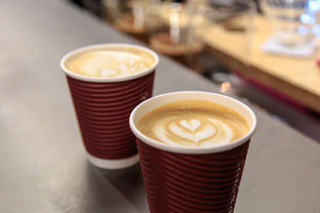 Side view of two latte art coffees with heart figure on, in take away paper glass in a cafe. Stock Photo