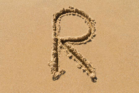 letter case: Letter R of the alphabet written on sand with upper case.