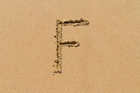 upper case: Letter F of the alphabet written on sand with upper case. Stock Photo
