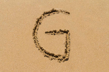 upper case: Letter G of the alphabet written on sand with upper case. Stock Photo
