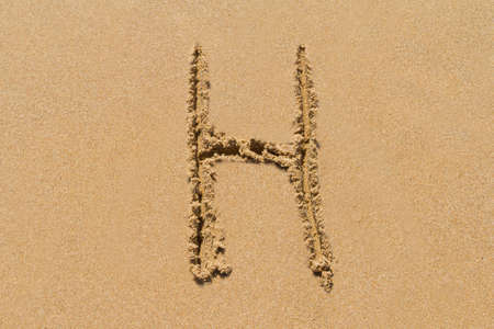 upper case: Letter H of the alphabet written on sand with upper case.