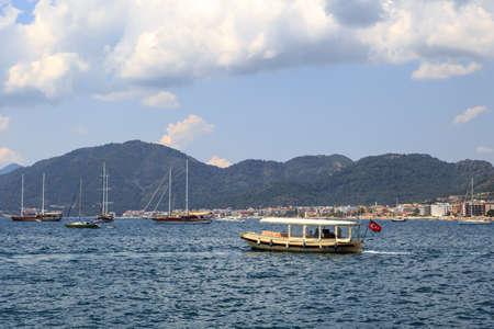 mugla: MUGLA, TURKEY - JUNE 1, 2015 : Boats sailing on Marmaris coast, under cloudy sky.