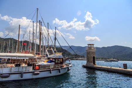 mugla: MUGLA, TURKEY - JUNE 1, 2015 : Sailboats anchored on harbor, ships in Marmaris Marina, on blue sky background.