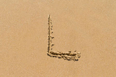 upper case: Letter L of the alphabet written on sand with upper case. Stock Photo