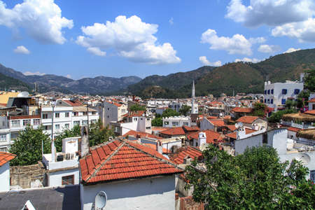 mugla: MUGLA, TURKEY - JUNE 1, 2015 : Top view of Marmaris town, roofs of the old houses, on cloudy sky background.