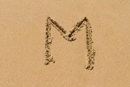 upper case: Letter M of the alphabet written on sand with upper case. Stock Photo