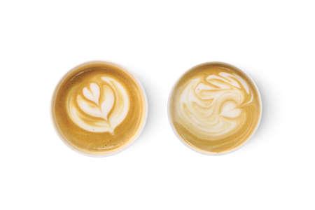 Bovenaanzicht van twee latte art koffie met hart figuur, op een witte achtergrond.