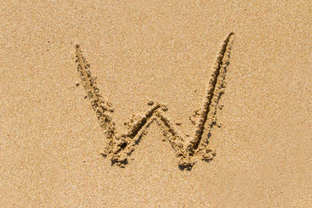 upper case: Letter W of the alphabet written on sand with upper case. Stock Photo