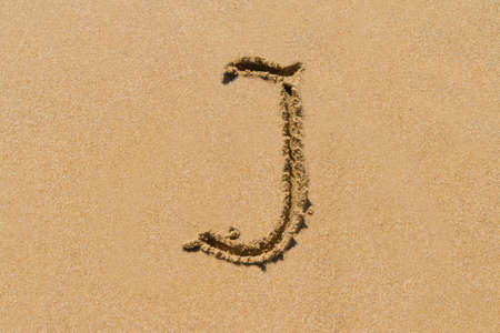 upper case: Letter J of the alphabet written on sand with upper case. Stock Photo