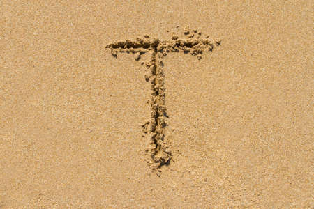 upper case: Letter T of the alphabet written on sand with upper case. Stock Photo